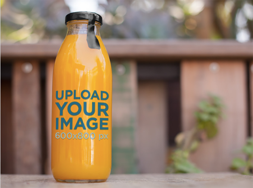 Label Mockup of a Juice Bottle Sitting on Top of a Table at a Patio