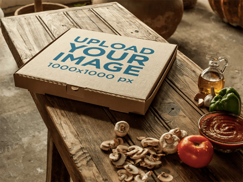Template of a Pizza Box Beside Ingredients on a Wooden Table
