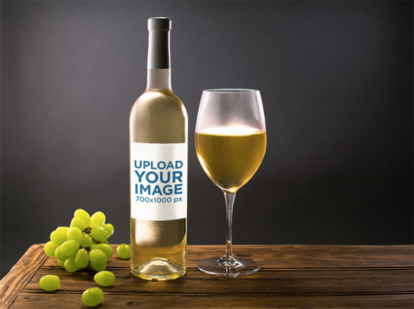 Template of a White Wine Bottle and a Glass with Grapes Nearby on a Wooden Table