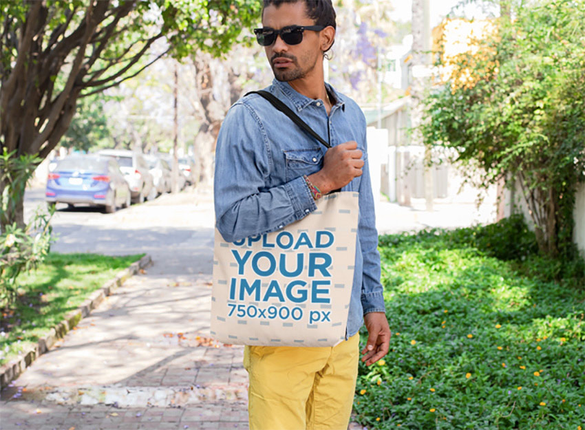 Mockup of a Man with Sunglasses Carrying a Tote Bag on His Shoulder