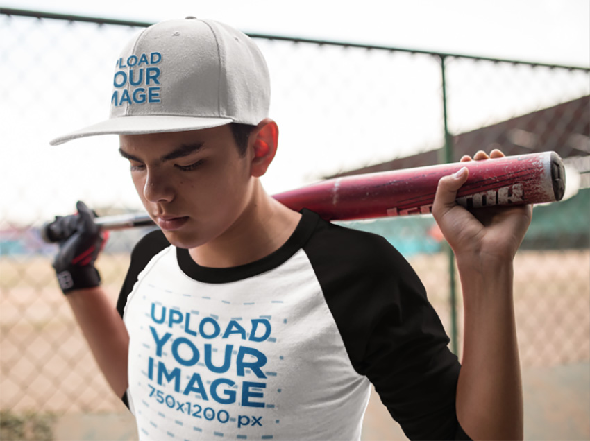 Boy Holding a Bat on His Shoulders Wearing a Baseball Hat Mockup and a Raglan Tee