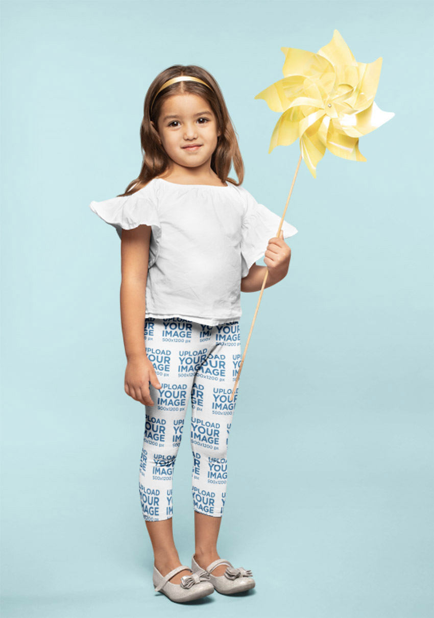 Mockup of a Little Girl Wearing Leggings Holding a Paper Windmill
