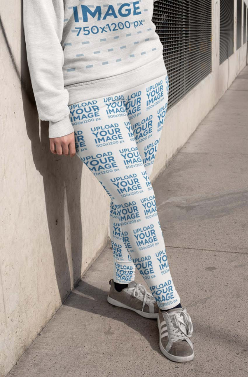 Mockup of a Woman Leaning Against a Concrete Wall Wearing Plus Size Leggings
