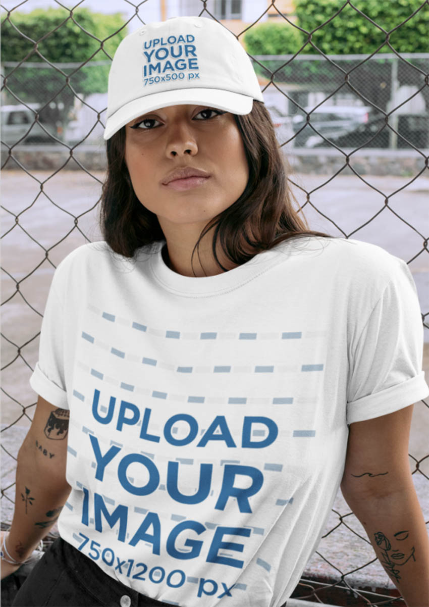 T-Shirt Mockup Featuring a Woman Wearing a Dad Hat by a Chain Link Fence