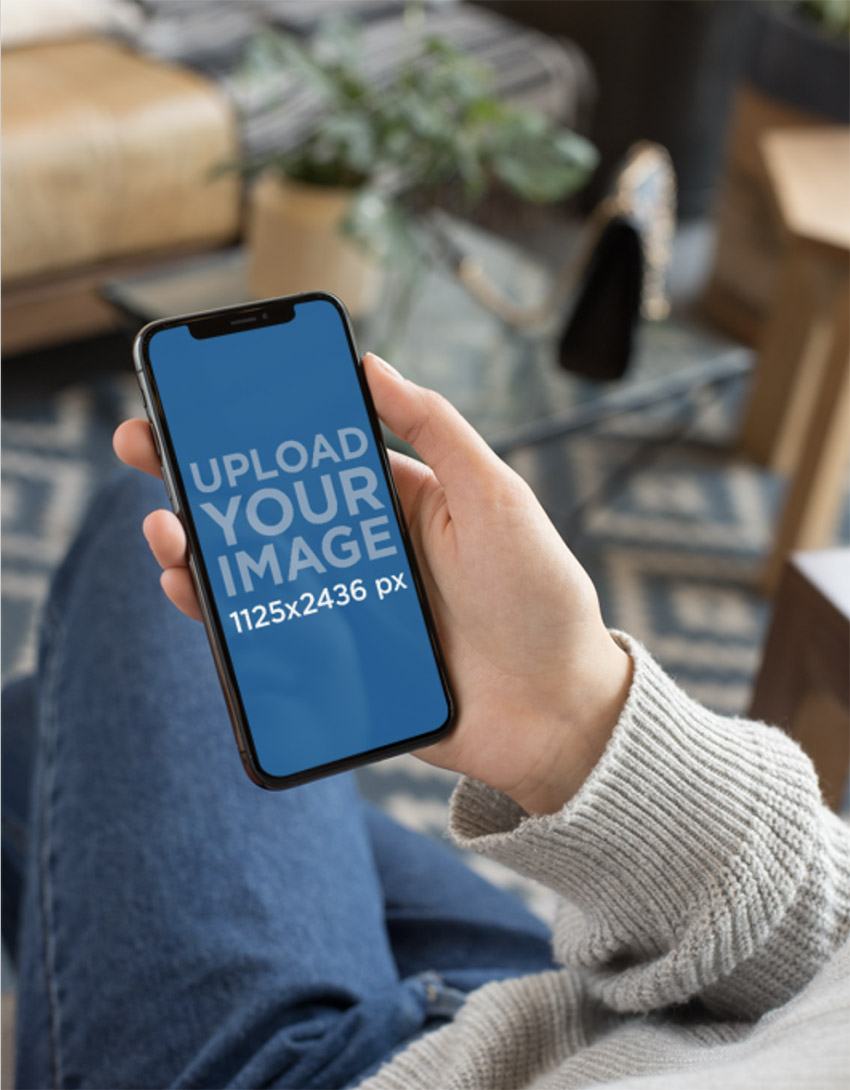 Mockup Featuring an iPhone 11 Pro Being Held by a Woman Sitting Down