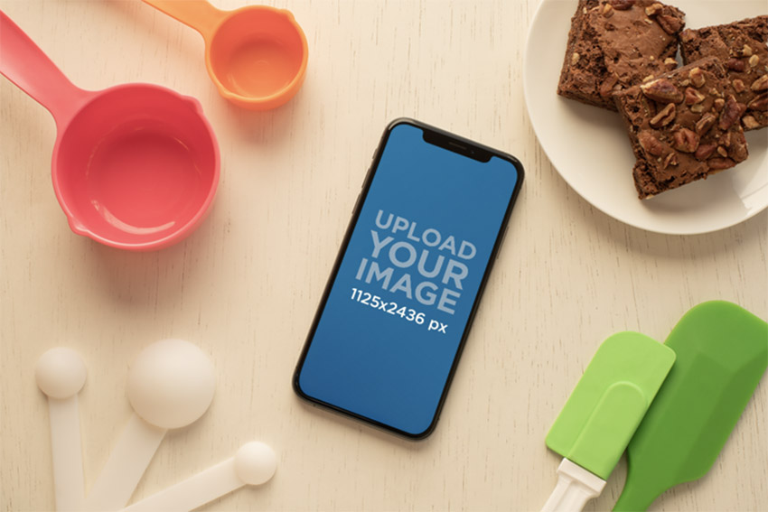 Mockup of an iPhone 11 Pro Surrounded by Baking Supplies