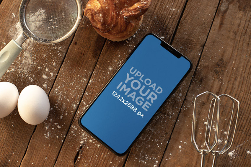 iPhone 11 Pro Max Mockup over a Wooden Surface Surrounded by Baking Supplies