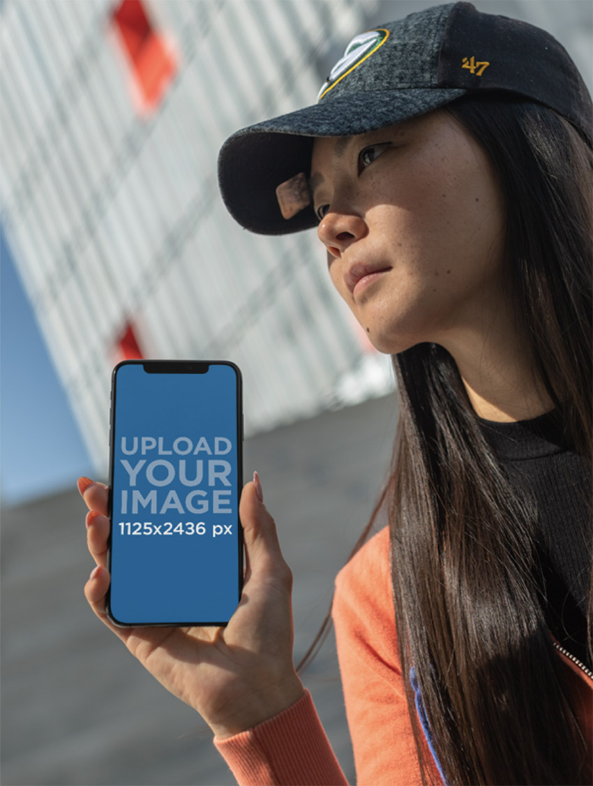 iPhone 11 Pro Mockup of a Long-Haired Woman with a Cap Staring into the Sky