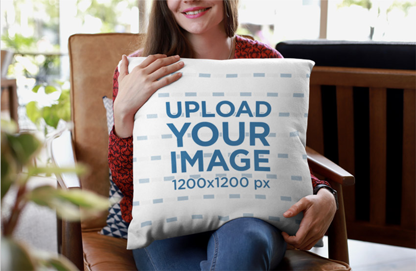Mockup of a Smiling Woman Holding a Pillow