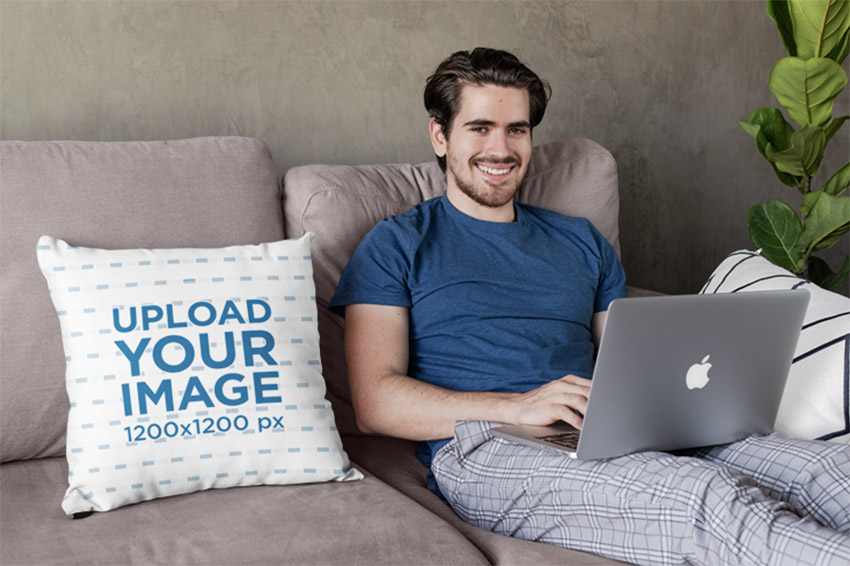 Square Pillow Mockup Featuring a Joyful Young Man Sitting on a Couch
