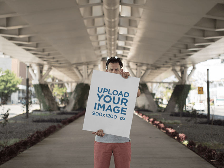 Hipster Dude Holding a Big Poster While Below a Beautiful White Bridge Mockup