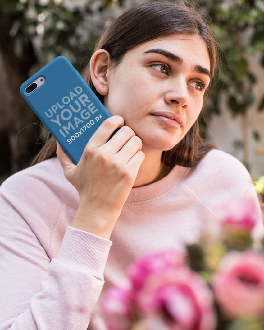 Mockup of a Woman Holding a Phone Case Near Flowers