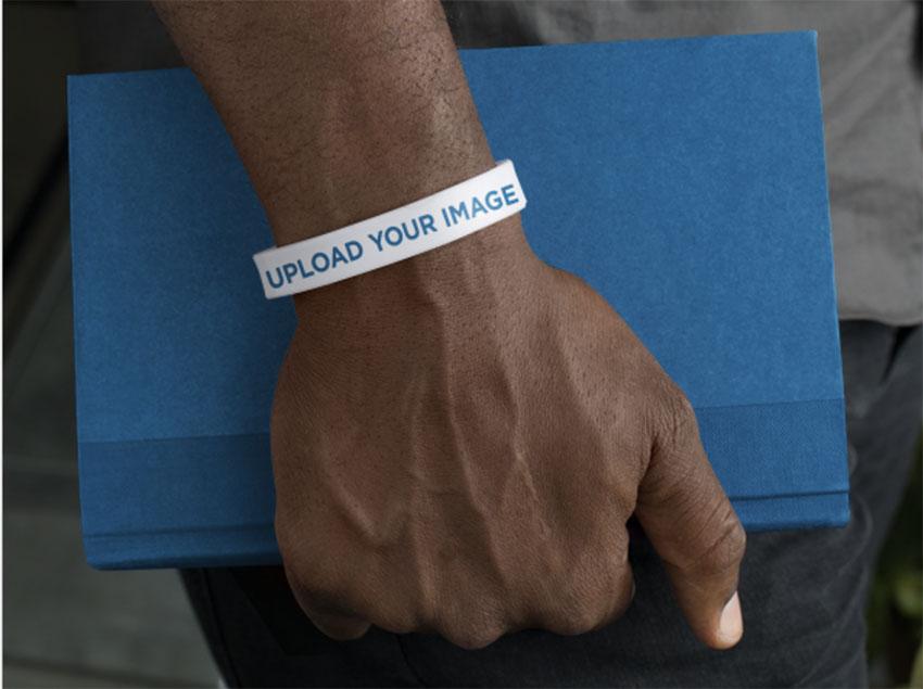 Logo Mockup - Silicone Wristband Mockup of a Man Holding a Book