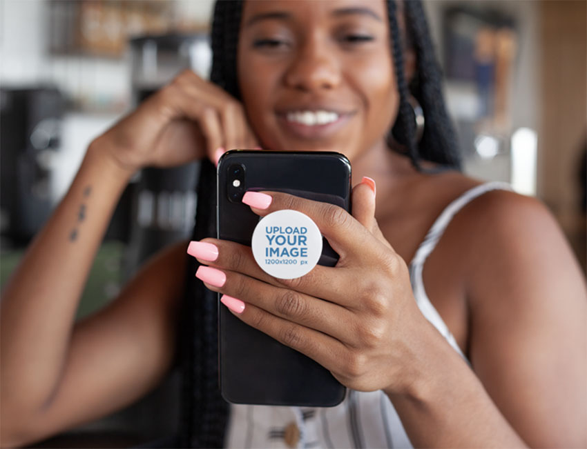 Phone Grip Mockup Featuring a Smiling Woman Looking at Her iPhone