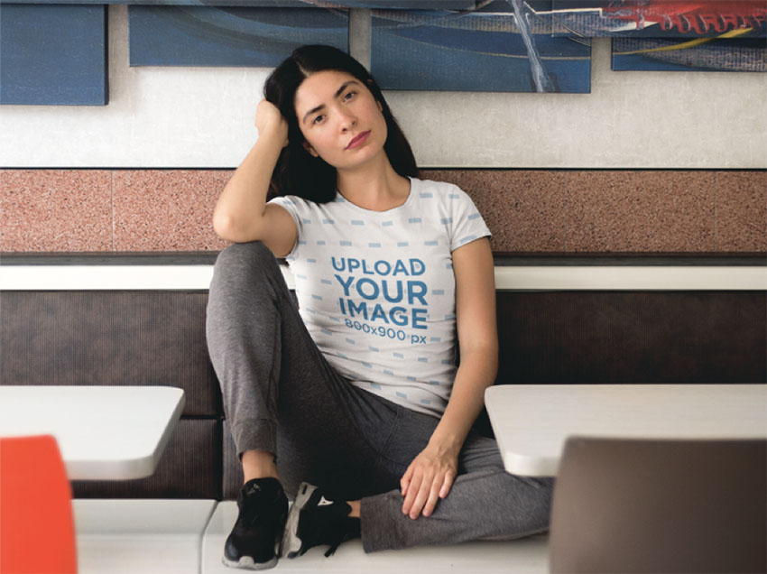 Pretty Woman Sitting Down in a Restaurant While Wearing a Sublimated T-shirt Mockup