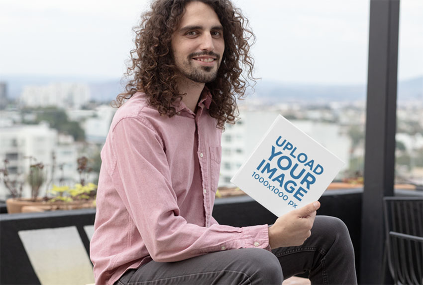 Mockup of a Smiling Man Holding a Square Hardcover Book