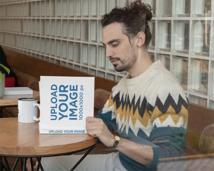 Square Book Mockup Fearing a Man Reading at a Cafe
