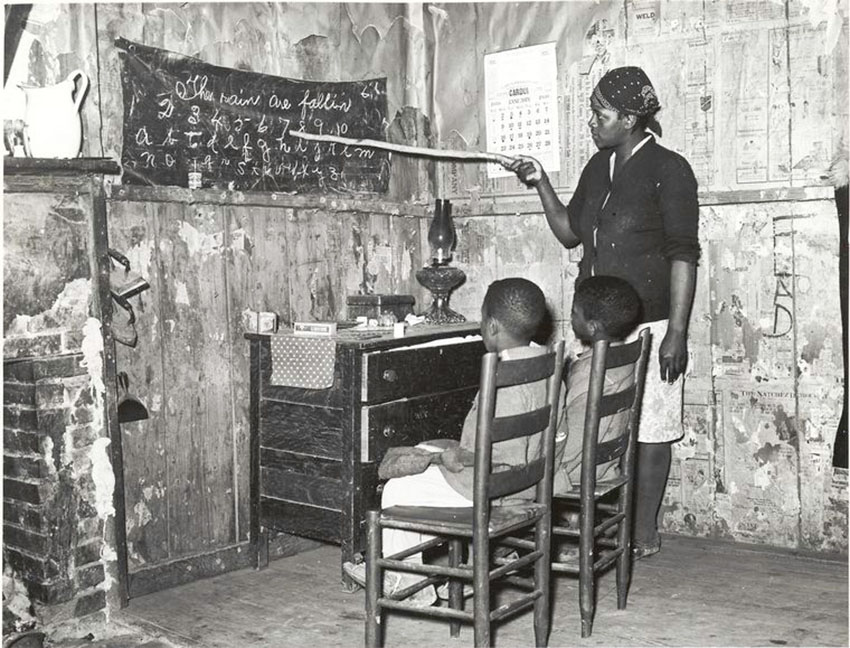 Mother teaching children numbers and alphabet in sharecropper's home, Louisiana. Source: Schomburg Center for Research in Black Culture