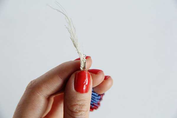 Take a box clasp cord end and gather all the tied strands inside the opening