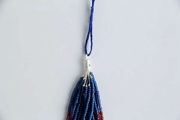 thread one end through the box clasp cord end on your beaded tassel