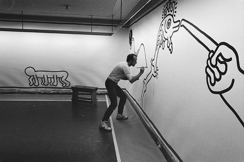 Keith Haring at work in the Stedelijk Museum in Amsterdam by Unknown Author is licensed under CC BY 40