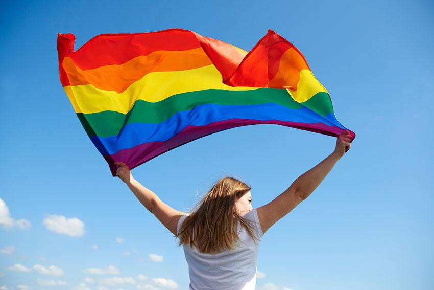 Girl holding Gilbert Bakers pride flag