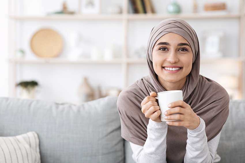 Smiling Woman Relaxing on Couch With Coffee a high-quality stock photo from Envato Elements