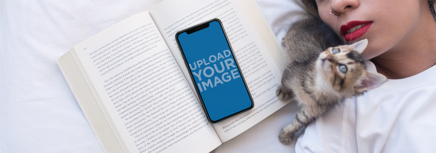Kitten Next to an iPhone X Mockup Lying Over a Book on a Girls Bed