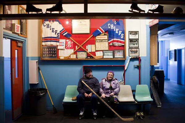 Bob Makolin and his wife Bertha sit on chairs surrounded by hockey memorabilia in the Calumet Colosseum