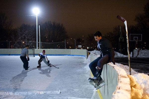 A sixteen-year-old boy hops over the side of a hockey rink to join play with his friends at an outdoor rink