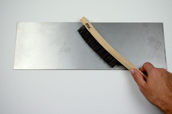 Use the wire brush to scrape the surface of the metal