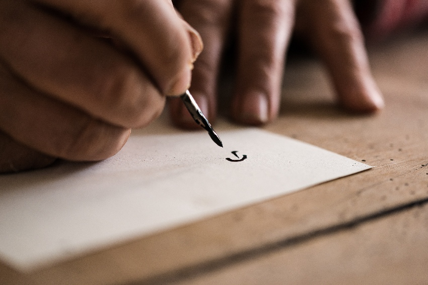 Person using a nib pen and ink to do calligraphy