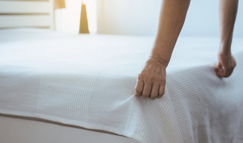cleaner making a bed