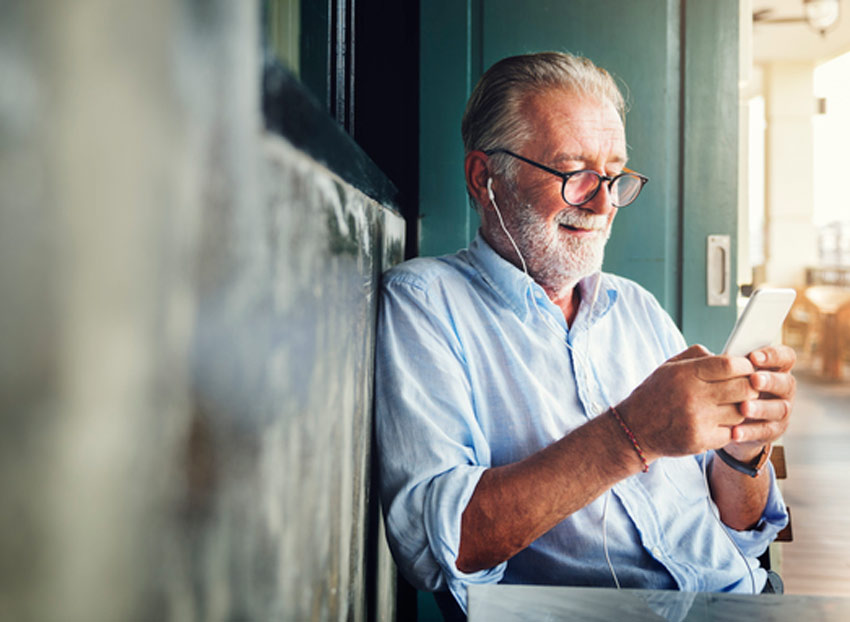Older bearded man in a cafe using a smartphone with earbuds