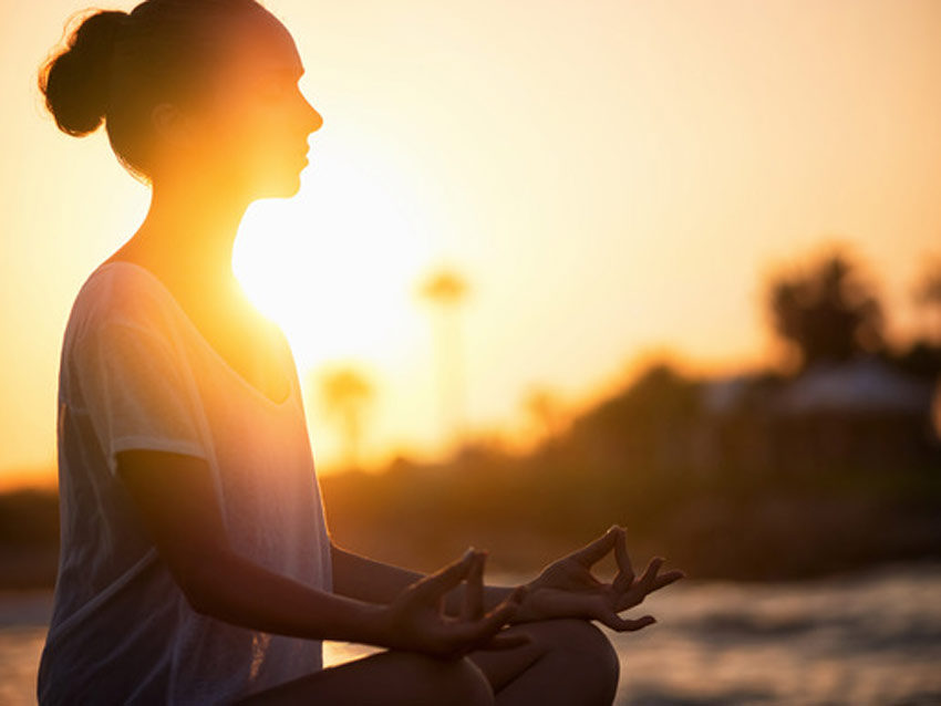 Woman sitting cross-legged meditating on the beach in front the setting sun
