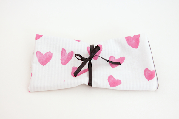Photo of patterned cloth with simple ribbon on neutral background