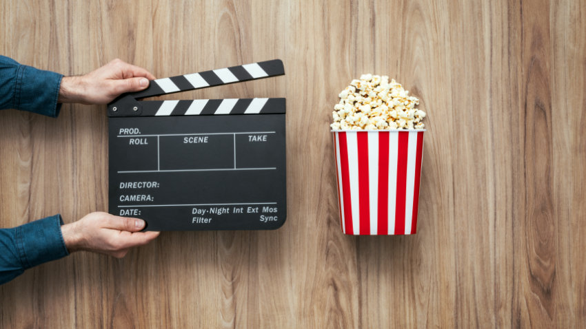 Hands holding a clapper board next to a box of popcorn
