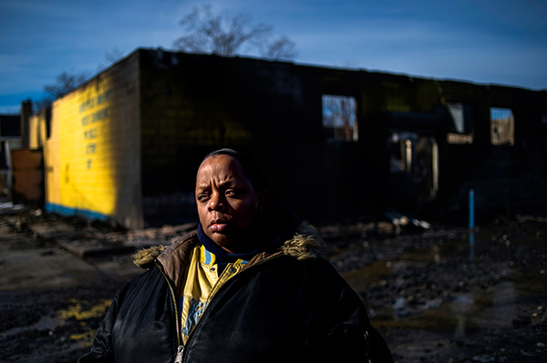Flint resident Andrea Cooper stands somberly outside of Liquor Plus located at 2407 Martin Luther King Avenue where a fully-engulfed blaze totaled the building on Monday Jan 26 2015 in Flint