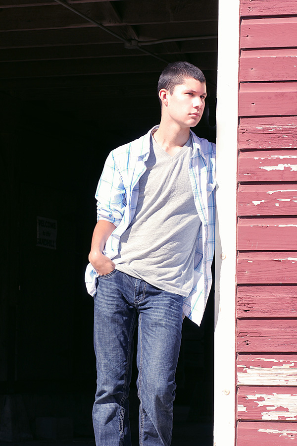 Young man standing in the doorway of a barn