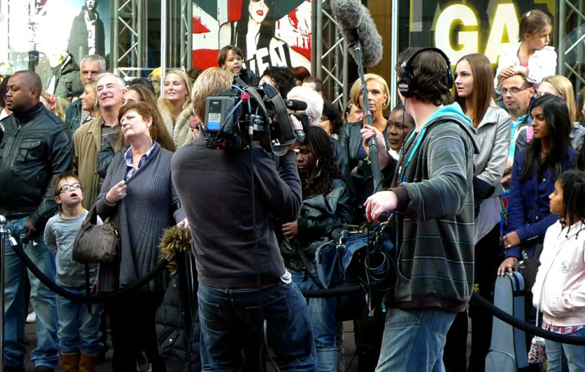 two person film crew and crowd