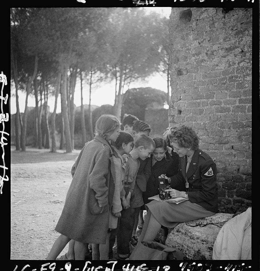 Toni Frissell sitting holding camera on her lap with several children standing around her somewhere in Europe