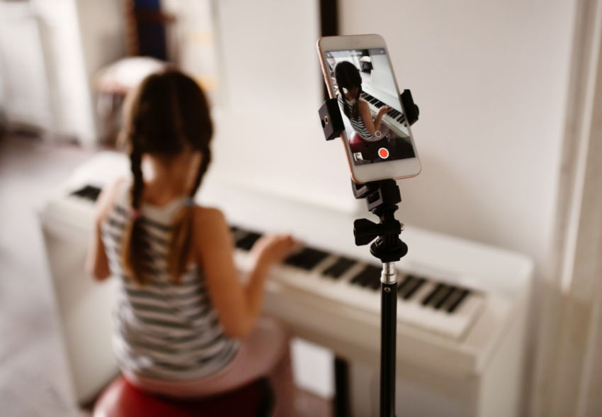 Child plays piano with cellphone in clip holder recording video