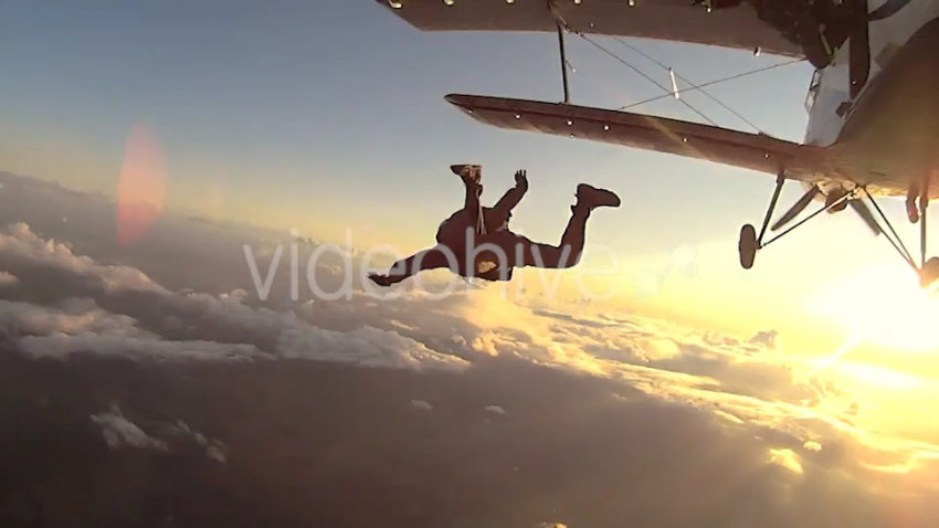 Skydiver jumping from a small airplane above a clound bank