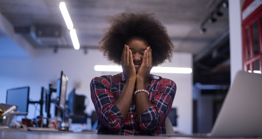 Woman holding her face with her hands in an office