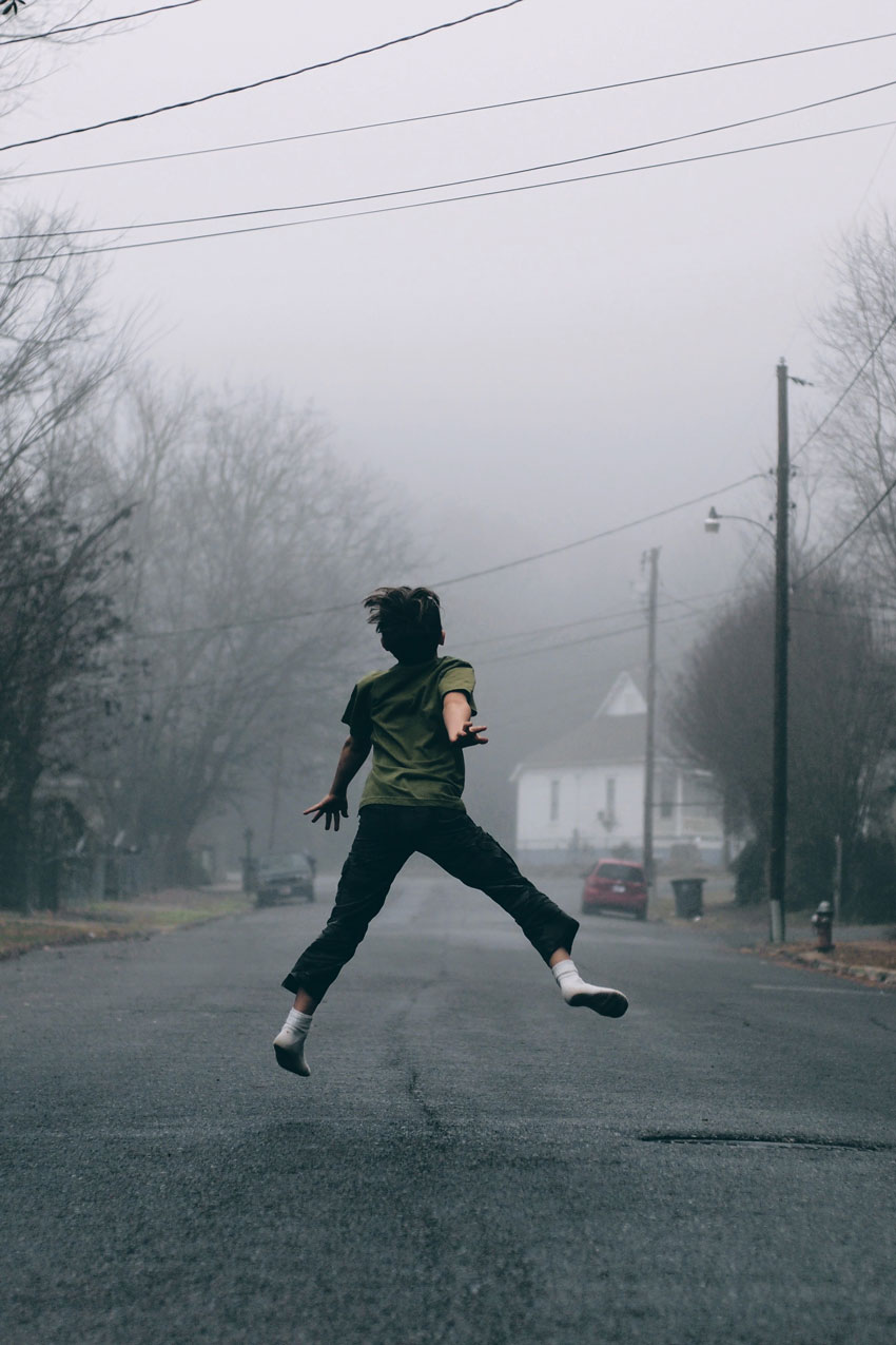 sample image of a person jumping in the air on an empty street in winter overcast day