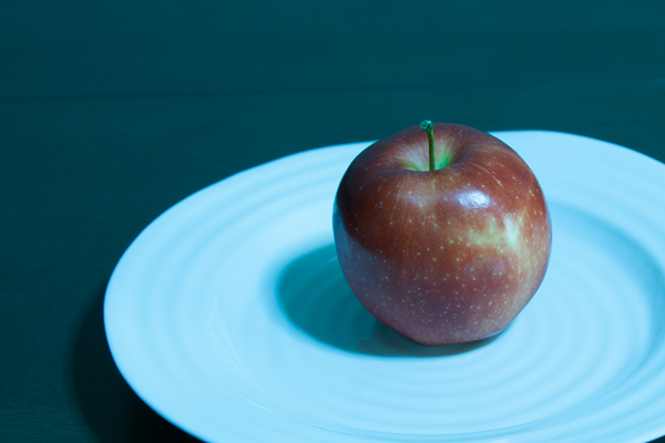 An apple on a white plate with colour cast