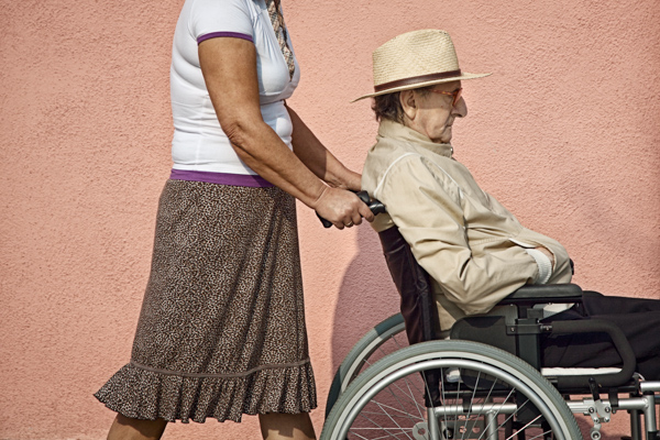 Woman pushing a proud-looking man in a wheelchair