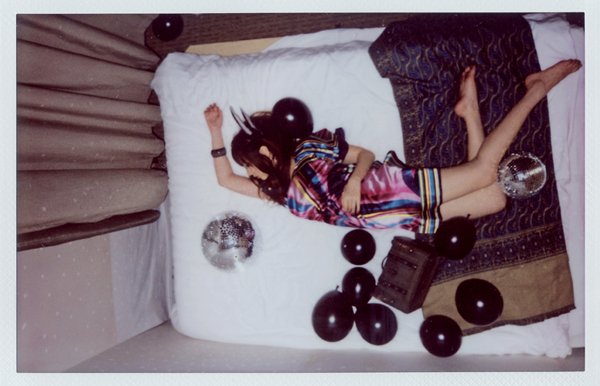 Woman lying on a bed with music albums
