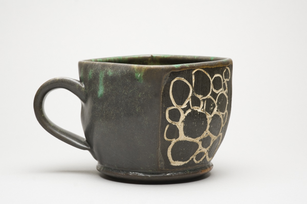 Ceramic mug with top opening and handle showing