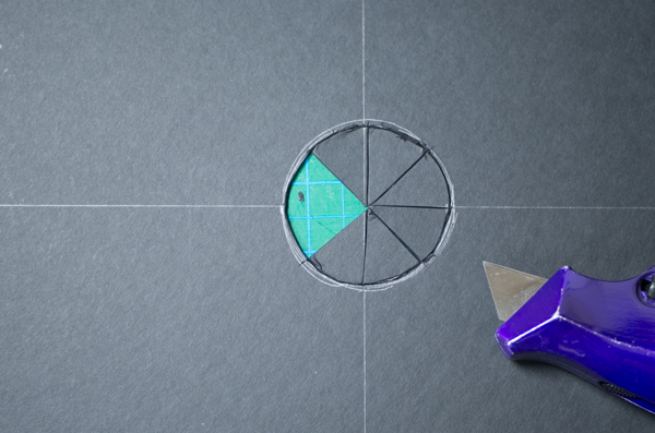 Cutting a circle opening in black mat board to create shoot-through flag